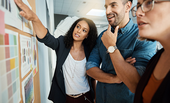 woman showing man and women chart on bulletin board